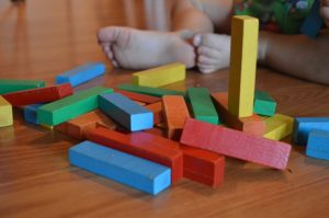 a child palying with colored blocks in a preschool class
