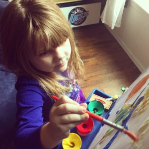 infant girl painting in preschool
